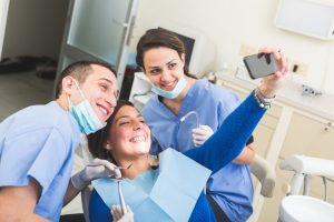 Happy Patient, Dentist and Assistant Taking Selfie All Together.